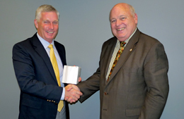 Robert M. Wells, Director of Training for the National and International Maritime Law Enforcement Academy,  right, presents a Document of Certification to William H. Watson, President of AdvanFort, attesting to the fact that he company's Counter Piracy Security Training programs meet or exceeds international standards. The certification followed a detailed audit of the programs.